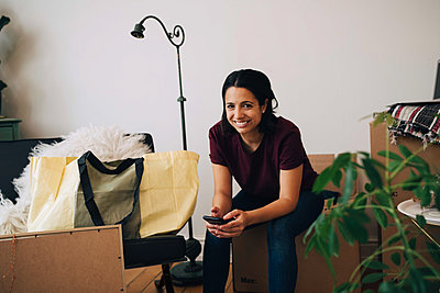 Portrait of smiling woman holding mobile phone while sitting on box against wall - p426m1542786 by Maskot