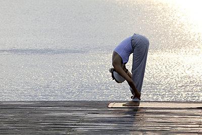 Frau macht eine Yogaübung auf einem Steg an einem See - p4903134 von T-Pool