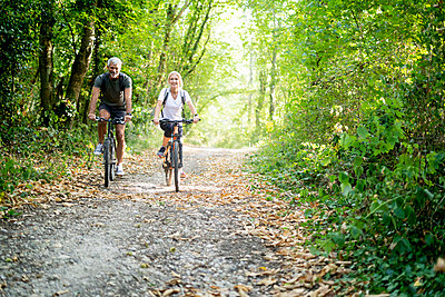 Portrait of smiling mature couple riding bicycles on footpath in forest - p623m2271735 by Frederic Cirou