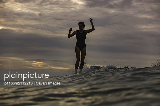 Young woman surfing at sunset - p1166m2112219 by Cavan Images