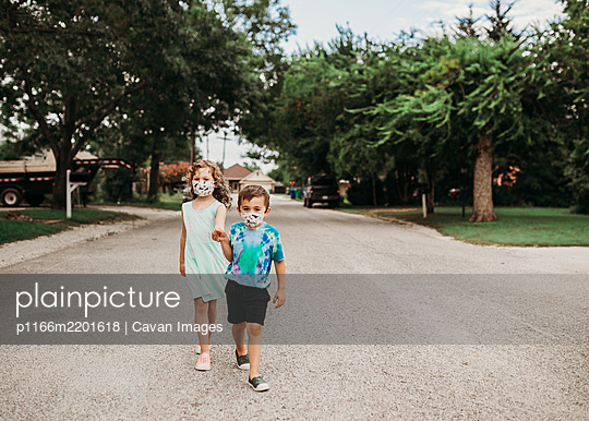 Young kids walking down street together wearing homemade masks - p1166m2201618 by Cavan Images