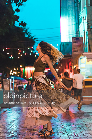 Thailand, Bangkok, young woman in the city dancing on the street at night - p300m1581428 von VITTA GALLERY