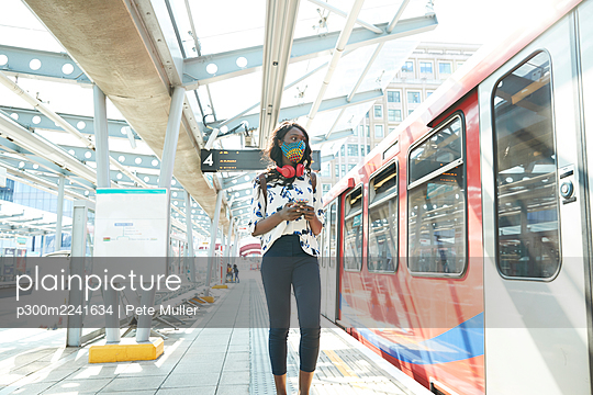 Businesswoman wearing face mask using mobile phone while standing at station platform - p300m2241634 by Pete Muller