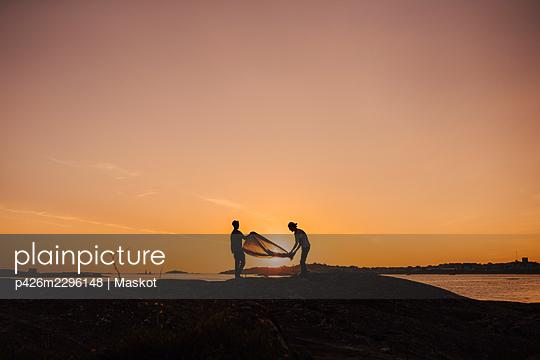 Gay couple preparing tent at lakeshore during camping - p426m2296148 by Maskot