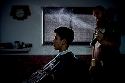 A barber spraying a customer's hair. - p1166m2212833 by Cavan Images