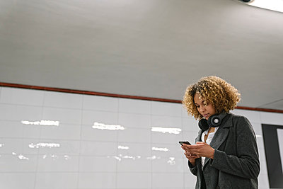 Woman using smartphone in subway station - p300m2143420 by Hernandez and Sorokina