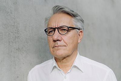 Portrait of a pensive senior businessman at a concrete wall - p300m2155360 by Joseffson