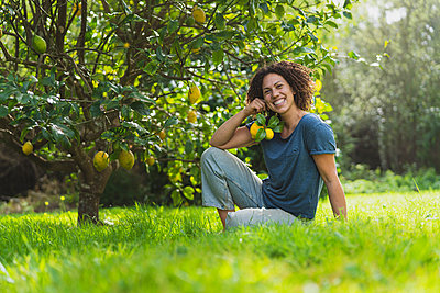 Happy woman holding lemons while sitting on grass under lemon tree - p300m2268090 by Steve Brookland