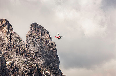 Helicopter flying above mountain peak, Corvara, Alta Badia South Tyrol, Italy - p429m872930 by Manuel Sulzer