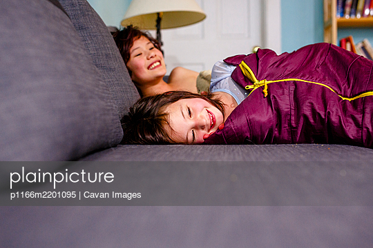 two happy smiling children lay together on a couch in sleeping bags - p1166m2201095 by Cavan Images