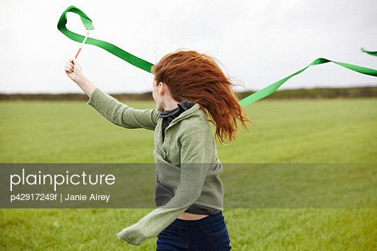 Teenage girl playing with ribbon - p42917249f by Janie Airey