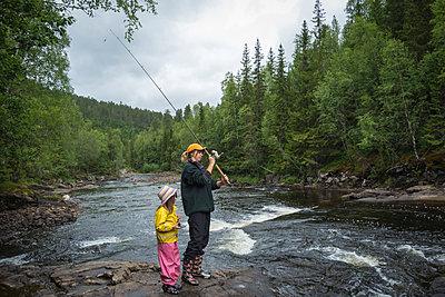 Junge Frau beim Angeln mit ihrer Tochter - p1418m2007554 von Jan Håkan Dahlström