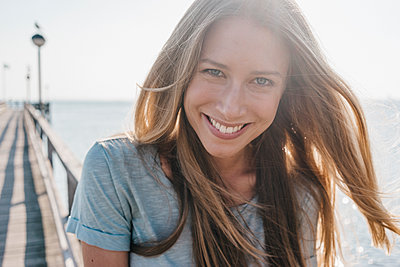 Portrait of happy young woman on jetty at backlight - p300m1205887 by Kniel Synnatzschke