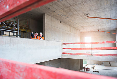 Two men wearing safety vests talking in building under construction - p300m1460088 by Daniel Ingold