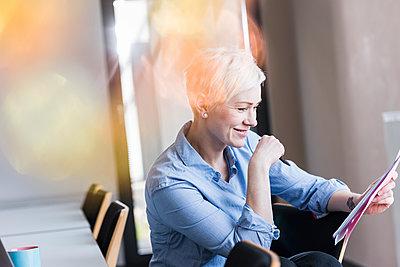 Smiling woman in office reading document - p300m1581635 von Uwe Umstätter