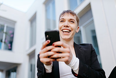 Close-up of cheerful trans young man using mobile phone while sitting against building - p300m2221399 by Tania Cervián
