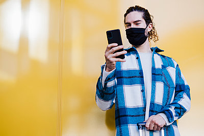 Young man wearing protective face mask using mobile phone while standing against yellow wall - p300m2242370 by Eva Blanco