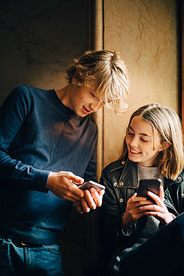 Smiling male and female friend using mobile phone while sitting at home - p426m1555929 by Maskot