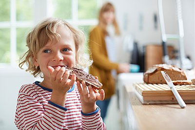 Young boy eating bread with chocolate spread, mother in background - p429m1062838 by Stephen Lux