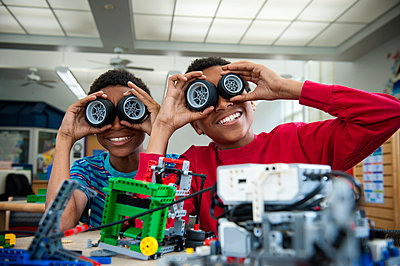 Boys playing with toy wheels in library - p555m1303536 by Stephen Simpson Inc
