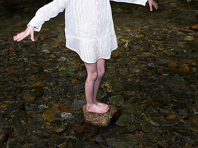 Girl standing on stone in water - p945m1589073 by aurelia frey