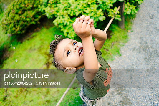 View from above of a young boy reaching upwards - p1166m2084232 by Cavan Images