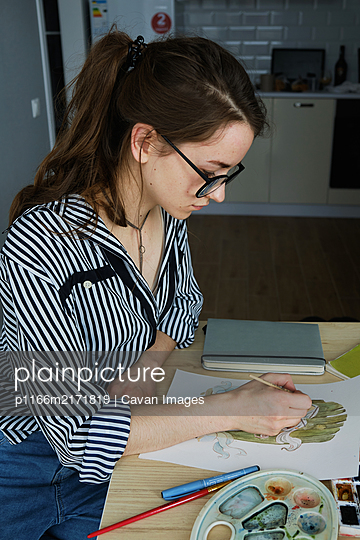 millennial girl draws fabulous images on paper while sitting at home - p1166m2171819 by Cavan Images