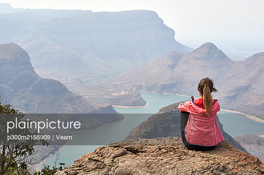 Woman sitting on a rock enjoying the beautiful landscape below her, Blyde River Canyon, South Africa. - p300m2155909 by Veam