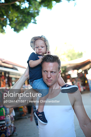 Father carrying son on shoulders - p312m1471597 by Helena Christerdotter