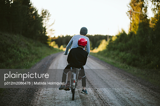 Boys riding bike on dirt track - p312m2086478 by Matilda Holmqvist