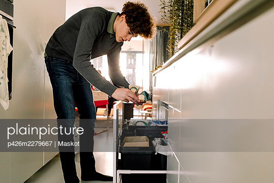 Full length of teenage boy throwing garbage in bin at home - p426m2279667 by Maskot
