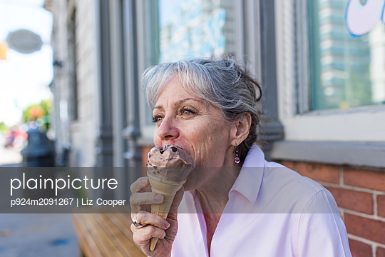 Senior woman sitting on sidewalk eating chocolate ice cream cone - p924m2091267 by Liz Cooper