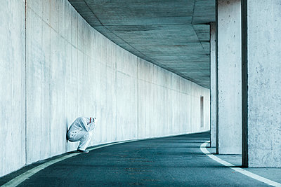Despaired man wearing protective clothing leaning against concrete wall in a tunnel - p300m2171382 by Valentin Weinhäupl