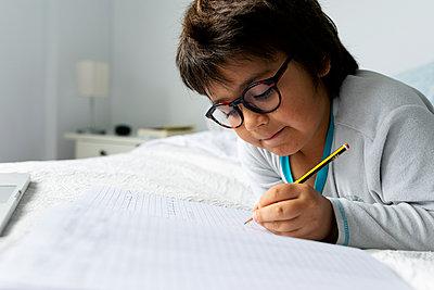 Portrait of little boy lying on bed doing homework - p300m2181155 by Valentina Barreto