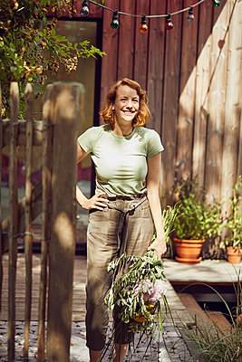 Smiling mid adult woman holding flowers while standing outside tiny house - p300m2214036 by Maya Claussen