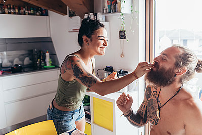 Bearded tattooed man with long brunette hair and woman with long brown hair in a kitchen, feeding each other. - p429m2201644 by Eugenio Marongiu