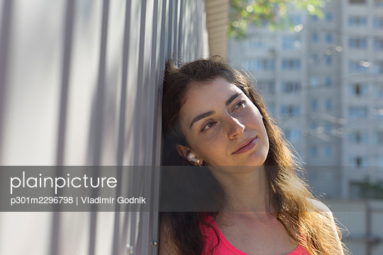 Serene young woman leaning against wall - p301m2296798 by Vladimir Godnik