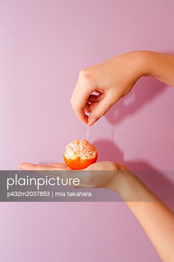 Frau zieht Haut von der Mandarine - p432m2037853 von mia takahara