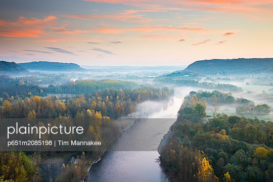 Aerial view of the Dordogne Valley & Dordogne river on a misty morning in autumn, Lot, Midi-Pyrenees, France - p651m2085198 by Tim Mannakee