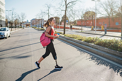 Sporty young woman with leg prosthesis walking in the city - p300m2171228 by Eugenio Marongiu