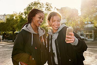 Teenage girls using smart phone - p352m2121191 by Folio Images