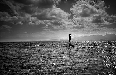 Silhouette of Caucasian boy standing on rock in ocean - p555m1301647 by Valeriya Tikhonova
