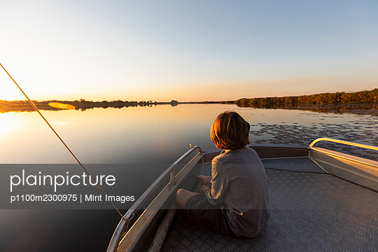 Young boy fishing at the stern of a boat on flat calm water - p1100m2300975 by Mint Images