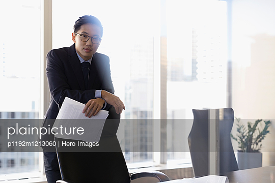 Portrait confident male lawyer holding paperwork in conference room
