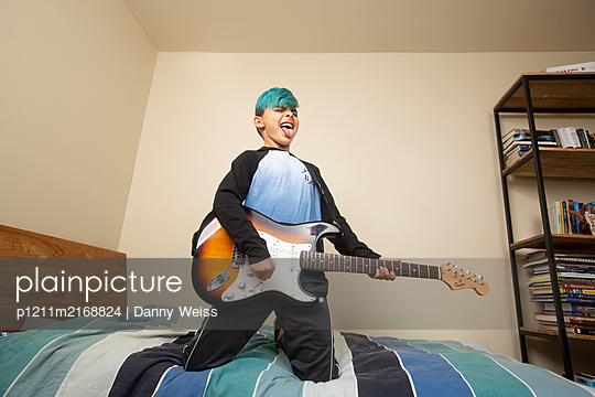 Boy on bed playing guitar - p1211m2168824 by Danny Weiss