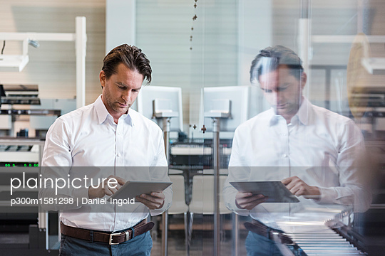 Businessman using tablet in modern factory - p300m1581298 von Daniel Ingold