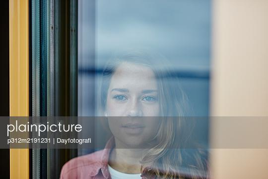 Woman looking through window - p312m2191231 by Dayfotografi