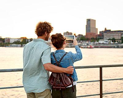 Paar mach Foto mit Tablet von Hamburg Panorama - p1124m1150167 von Willing-Holtz