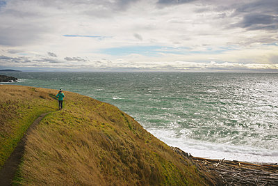 Rear view of woman walking on rock formation by sea against cloudy sky - p1166m1403158 by Cavan Images