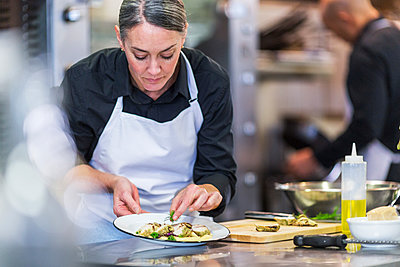 Female chef garnishing food while coworker working in background at restaurant - p1166m1423407 by Cavan Images